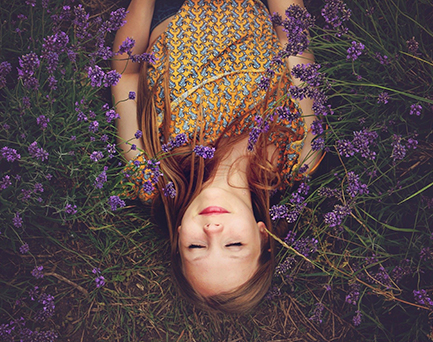 Happy teen girl laying peacefully in purple flower